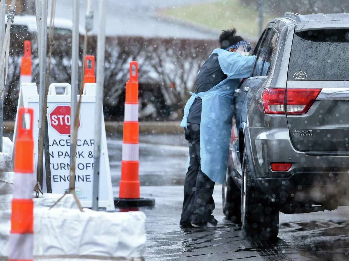 A health care worker takes a specimen at the Griffin Health drive-thru COVID-19 Test Collection Site at the Griffin Hospital campus parking lot in Derby on March 23, 2020.