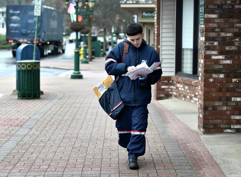 Branford, Connecticut - Monday, March 23, 2020: United States Postal employee Sammy Estrada delivers mail to a downtown Branford businesses and second story apartments above the businesses, most of whom are closed due to the Covid-19 / Coronavirus pandemic.