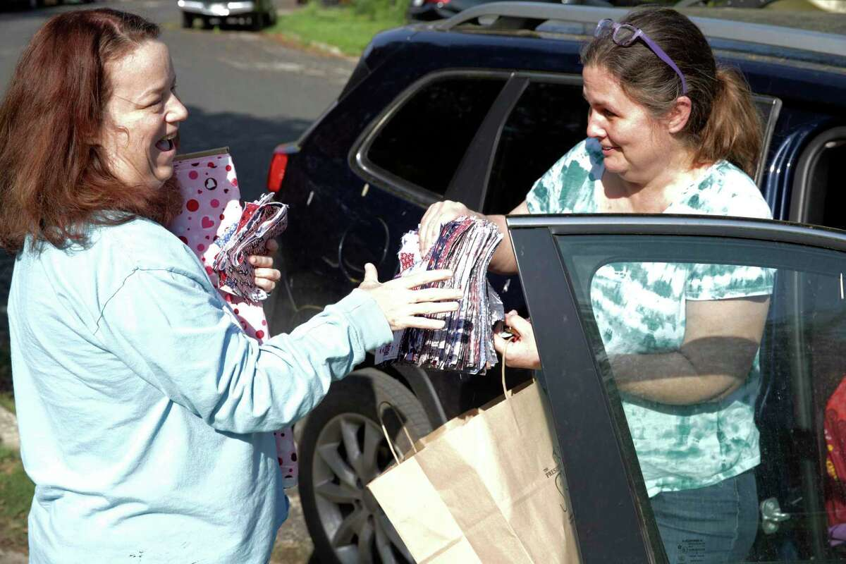 Bess Burton happily accepts a donation of fabric from friend Laura Stewart for surgical masks she is sewing at home and donating.