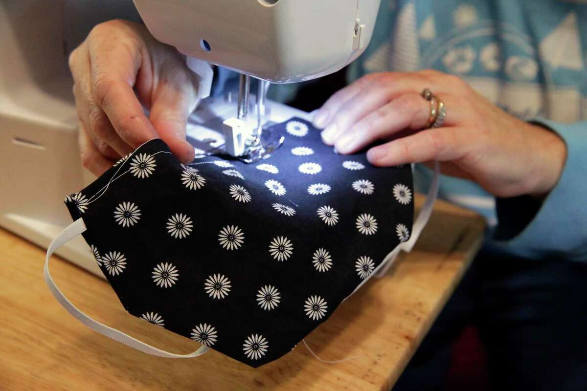 Bess Burton sews an elastic band into place on a surgical mask.