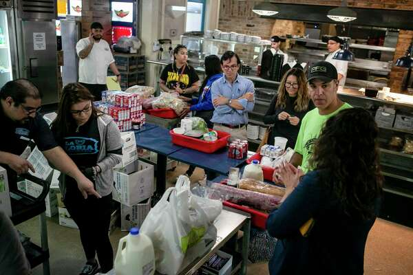 Customers wait in line to check out at La Gloria at the Pearl, which has become a makeshift grocery store.