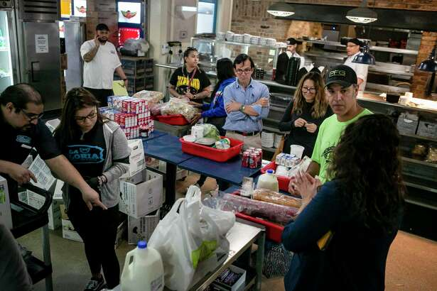 Customers wait in line to check out at La Gloria at the Pearl, chich has become a makeshift grocery stores.
