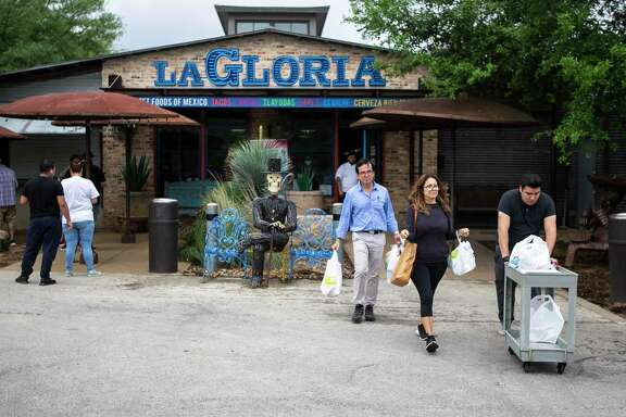 Robert Garcia, in blue shirt, and Teresa Garcia leave La Gloria at the Pearl after getting groceries there. Some local restaurants have created makeshift grocery stores amid coronavirus related shut downs.