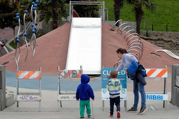 A local mom and her two boys stop at the closed Helen Diller Playground in Dolores Park following Mayor London Breed's decision to have city parks close children's playgrounds to prevent the spread of the coronavirus in San Francisco, Calif., on Monday, March 23, 2020.