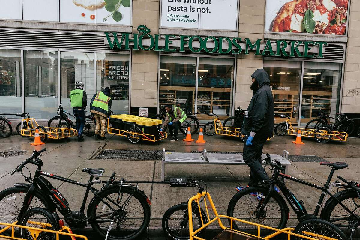 Online orders are loaded onto bikes at Whole Foods in Manhattan, March 17, 2020. The coronavirus has caused a surge in demand for grocery deliveries. (Bryan Banducci/The New York Times)