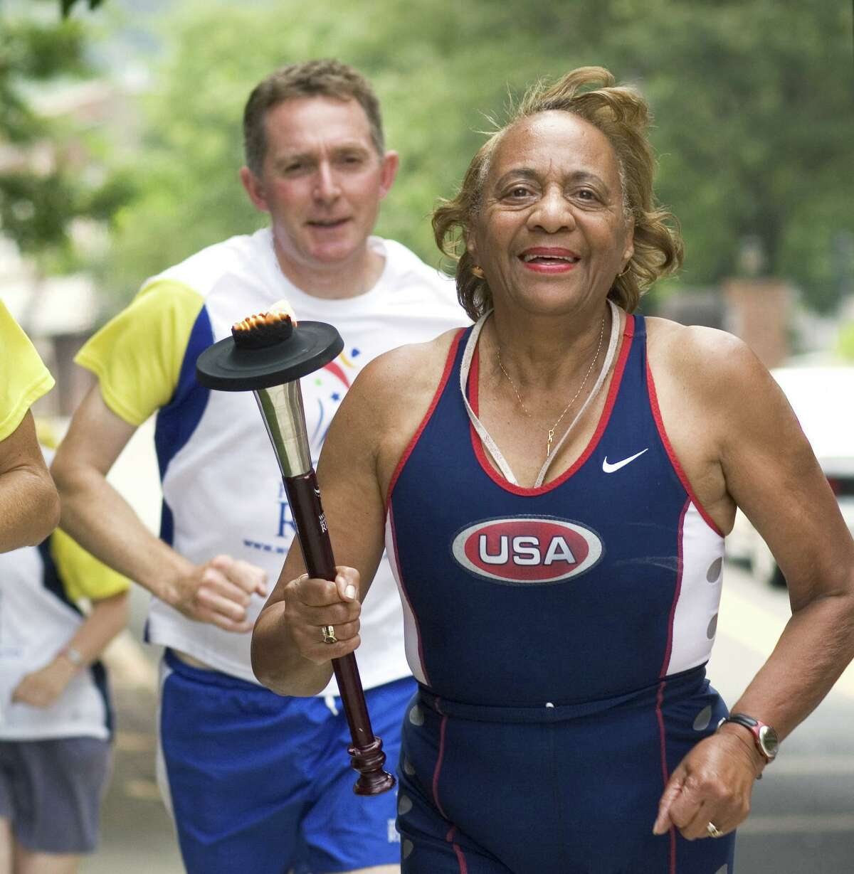 Mary Roman, former city clerk for the City of Norwalk, right, carries the torch during the World Harmony Run as it makes its way through Norwalk in 2008. Roman is trying to raise funds to compete in the World Masters Games in Australia.