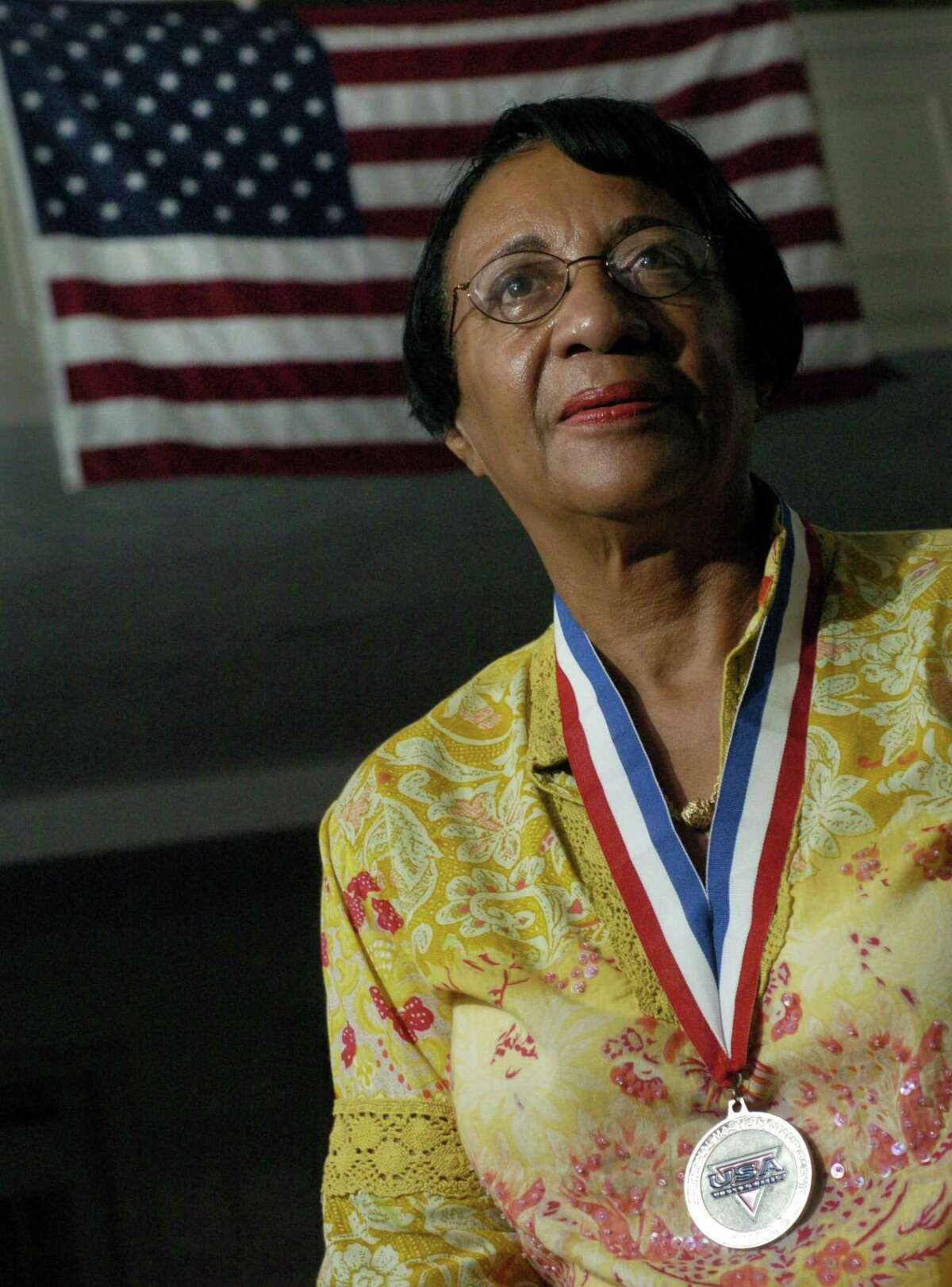 Norwalk_081304_ Mary Roman, Assistant City Clerk for the city of Norwalk, with her second place medal for hammer throw in the 2004 National Masters Championship. Roman, 68, took up track 13 years ago and is now qualified for the 2005 Senior Olympics. Kathleen O'Rourke/staff photo
