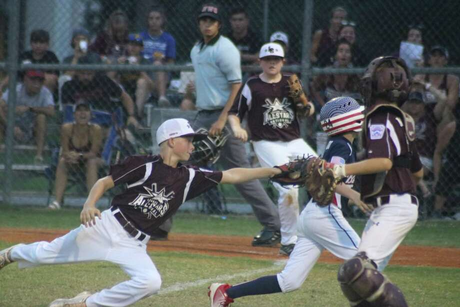 League City National All-Star Jacob Newsom makes a diving tag on a Bayside Little League runner during last summer's District 14 championship game for the 12-year-olds. Now the question on everyone's mind, will there be a championship game this summer? Photo: Robert Avery