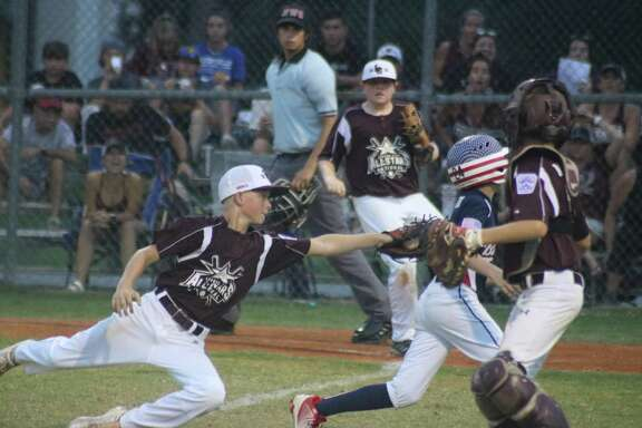 League City National All-Star Jacob Newsom makes a diving tag on a Bayside Little League runner during last summer's District 14 championship game for the 12-year-olds. Now the question on everyone's mind, will there be a championship game this summer?