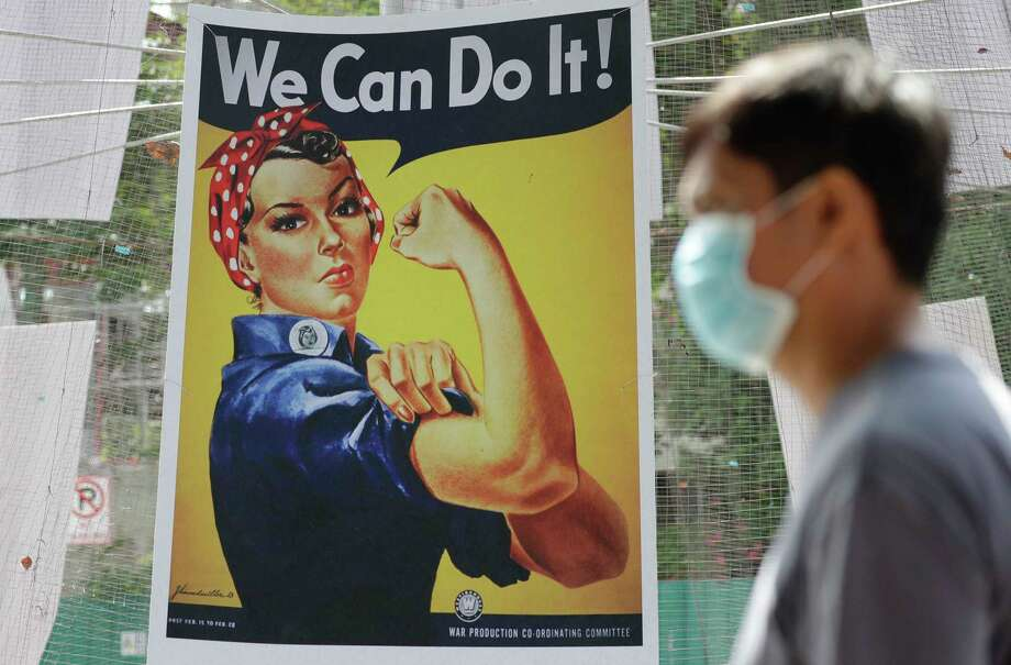A man wearing a protective mask walks beside a poster of American WWII icon Rosie the Riveter, at the Quezon city hall where volunteers and workers help prepare food during the community quarantine aimed to prevent the spread of the new coronavirus in Manila, Philippines, Tuesday, March 24, 2020. For most people the new coronavirus causes only mild or moderate symptoms, but for some it can cause more severe illness. Photo: Aaron Favila, AP / Copyright 2020 The Associated Press. All rights reserved.
