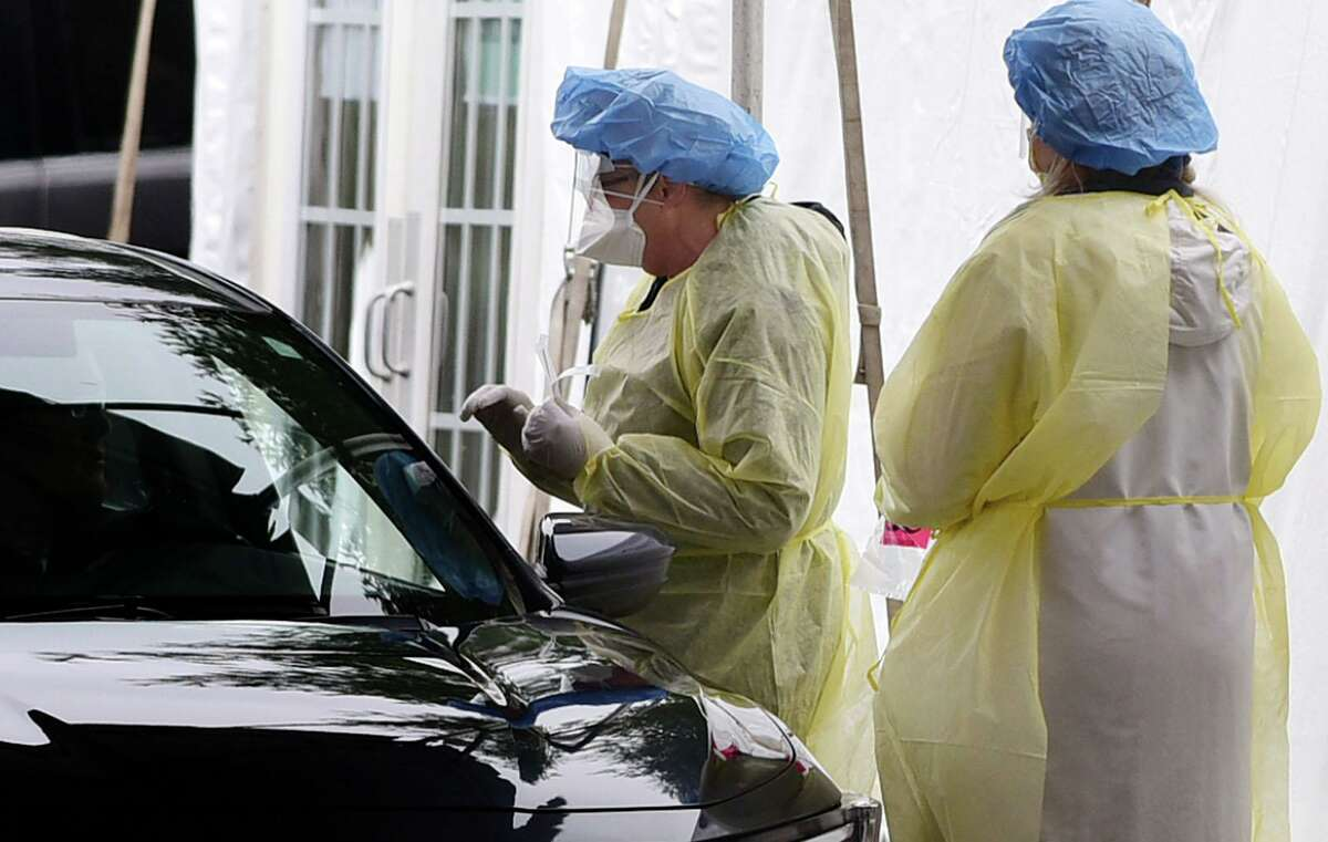 Hospital workers in Personal Protective Equipment collect samples for coronavirus testing at a drive-up faciltiy in the parking lot at Norwalk Hospital Thursday, March 19, 2020, in Norwalk, Conn. Testing is by appointment only with a doctors referral.
