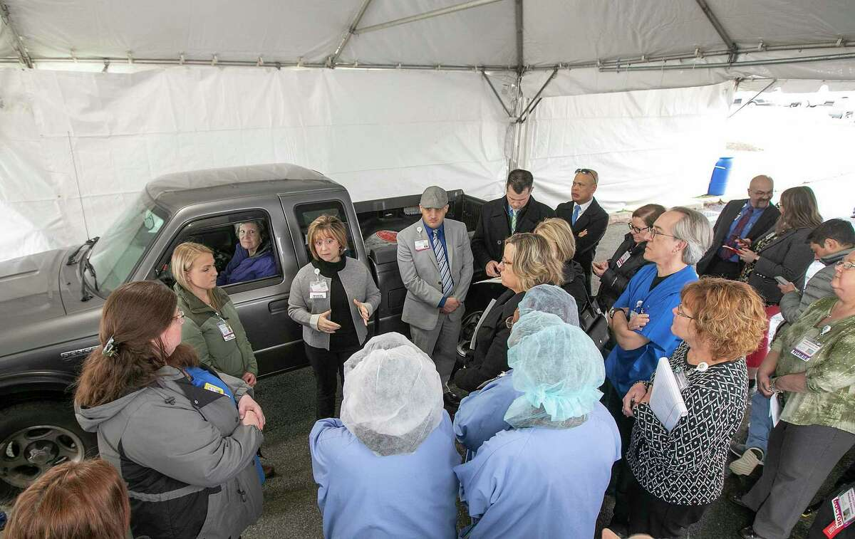 Nurse leader Karen Fasano gives instruction to medical personnel while practicing drive-through testing for the coronavirus at MidState Medical Center in Meriden, Conn., on March 17, 2020.