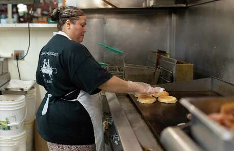 Jessica, who declined to give their full name, prepares an order at the Fish Pond Restaurant kitchen, Saturday, March 21, 2020. The restaurant began working with a skeleton crew after the states announcement to close all dine-in services.