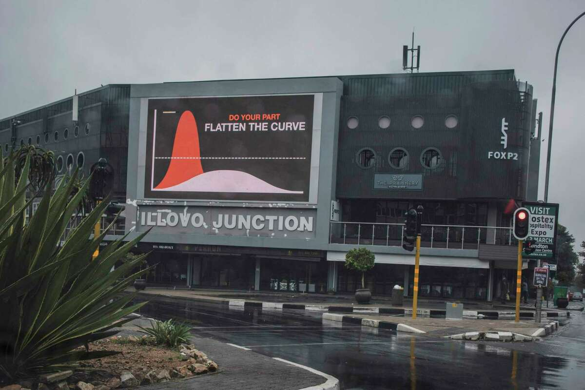 An electronic sign displays a message urging citizens to stay indoors to flatten the curve of the infections related to the COVID-19 Coronavirus at an empty intersection in Johannesburg.