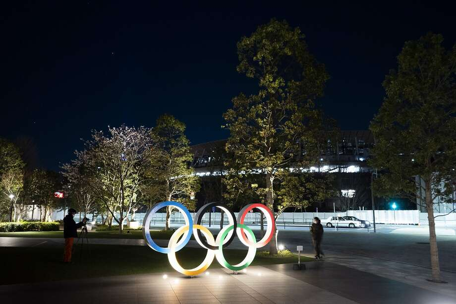 """The Olympic rings stand near the New National Stadium in Tokyo, Tuesday, March 24, 2020. IOC President Thomas Bach has agreed """"100%"""" to a proposal of postponing the Tokyo Olympics for about one year until 2021 because of the coronavirus outbreak, Japanese Prime Minister Shinzo Abe said Tuesday. (AP Photo/Jae C. Hong) Photo: Jae C. Hong / Associated Press"""