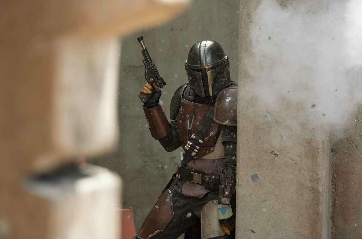 """This image released by Disney Plus shows Pedro Pascal in a scene from """"The Mandalorian."""" The streaming service is one of the big winners as Americans staying at home to avoid spreading the coronavirus are signing up for new offerings."""