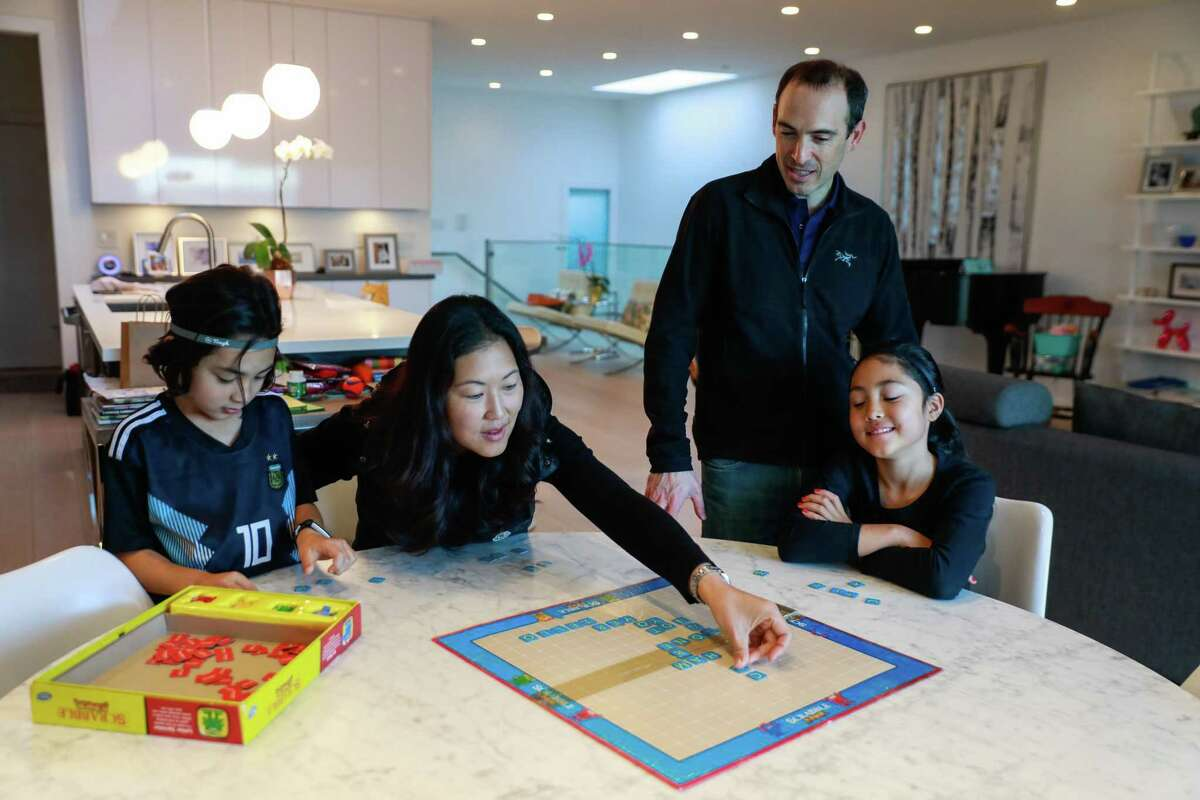 Ethan Ellis,6, mom Youjeong Kim, dad Ben Ellis and sister Emmy Ellis, 8 play scrabble at their dining room table at their home on Monday, Dec. 23, 2019 in San Francisco, California.