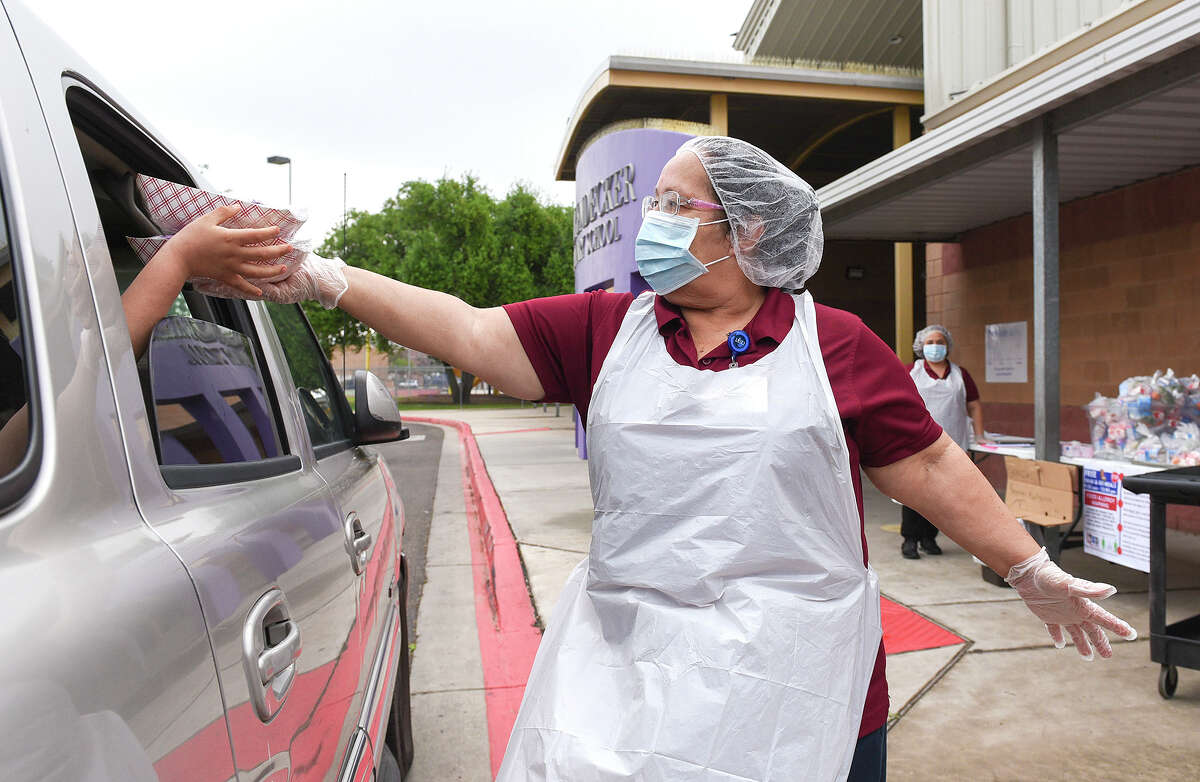 Cafeteria workers Edna Cassiano hands out breakfast and lunch packs to students, Mar. 23, 2020, during the LISD Grab and Go meal program at J.Z. Leyendecker Elementary School.