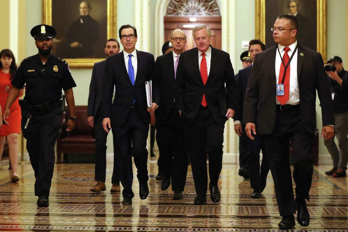 Treasury Secretary Steven Mnuchin (2L), White House Director of Legislative Affairs Eric Ueland (3L) and White House Chief of Staff Mark Meadows) arrive at the Capitol to continue negotiations on a $2 trillion economic stimulus in response to the coronavirus pandemic. After days of tense negotiations -- and Democrats twice blocking the nearly $2 trillion package -- the Senate and Treasury Department appear to have reached important compromises on legislation to shore up the economy during the COVID-19 pandemic.