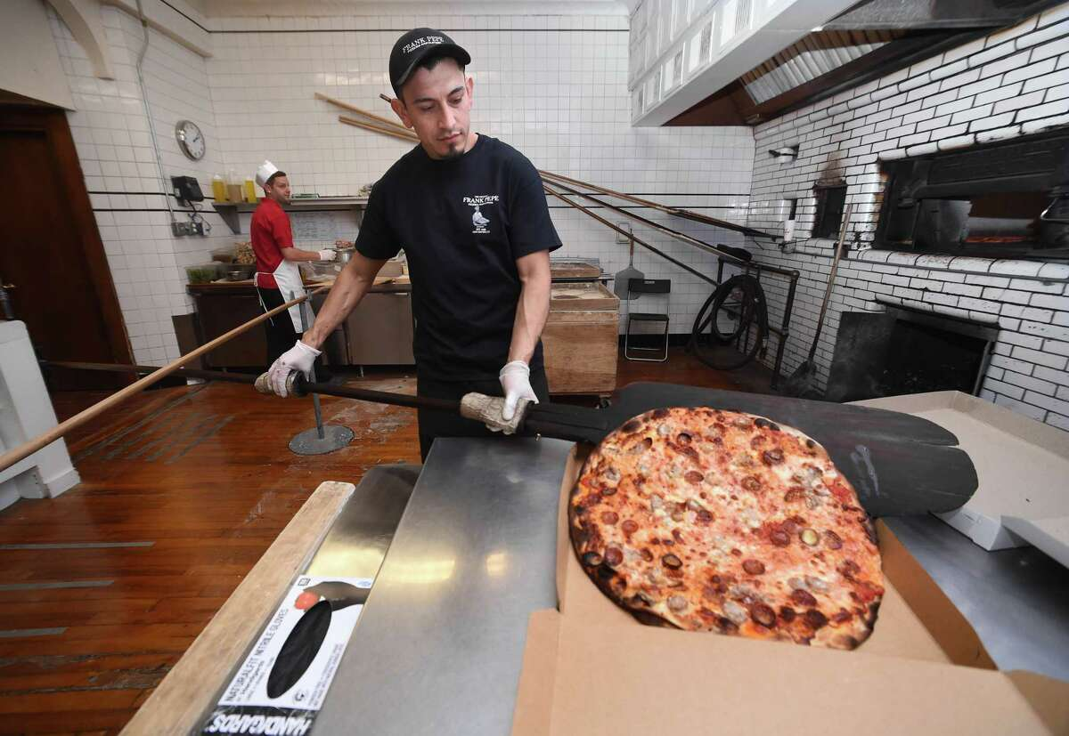 Sergio Juarez boxes a pizza for pickup at Frank Pepe Pizzeria Napoletana on Wooster Street in New Haven on March 23, 2020.
