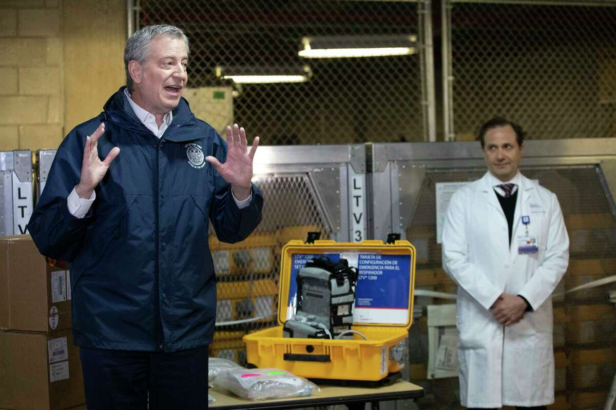 New York City Mayor Bill de Blasio, left, discusses the arrival of a shipment of 400 ventilators with Dr. Steven Pulitzer, the Chief Medical Officer of NYC Health and Hospitals, at the city's Emergency Management Warehouse., Tuesday, March 24, 2020, in New York.