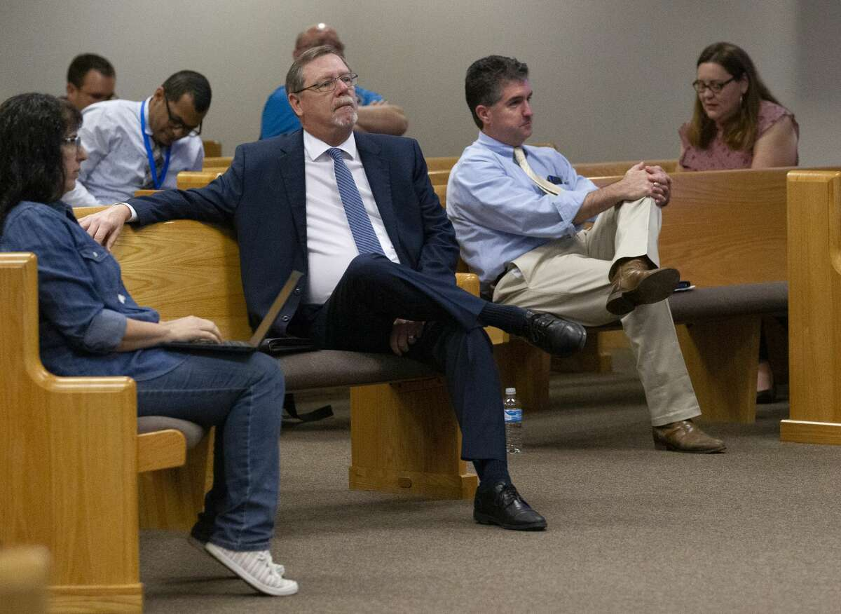 Montgomery County Attorney B.D. Griffin, center, is seen as attendees work to implement social distancing during a Montgomery County Commissioners Court meeting, Tuesday, March 24, 2020, in Conroe. Montgomery County Judge Mark Keough did not issue a stay-at-home order.