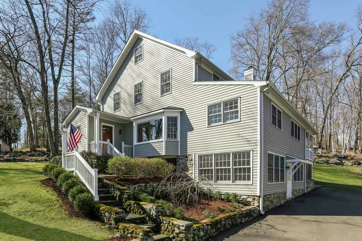 The beige colonial farmhouse at 66 Partrick Road in the Old Hill neighborhood sits on a 1.11-acre level and sloping property that the homeowners call