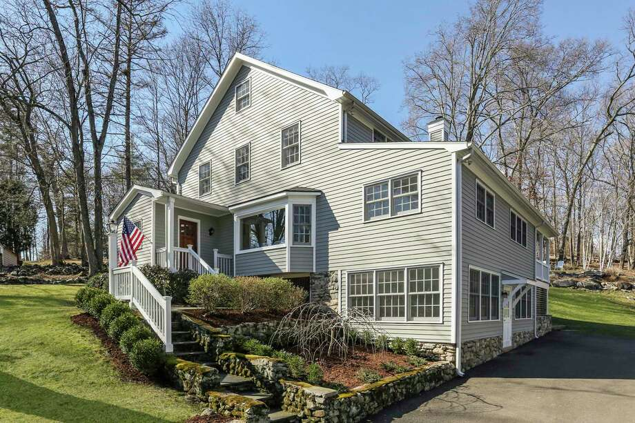 "The beige colonial farmhouse at 66 Partrick Road in the Old Hill neighborhood sits on a 1.11-acre level and sloping property that the homeowners call ""magical."" Photo: Ree_ann_macachor"
