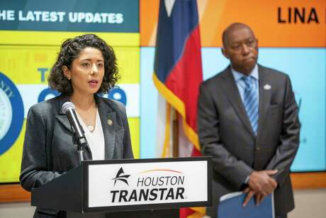 """Harris County Judge Lina Hidalgo speaks as Houston Mayor Sylvester Turner listens during a press conference announcing that the county will adopt a """"Stay Home, Work Safe"""" strategy until April 3, Tuesday, March 24, 2020, at TranStar in Houston."""