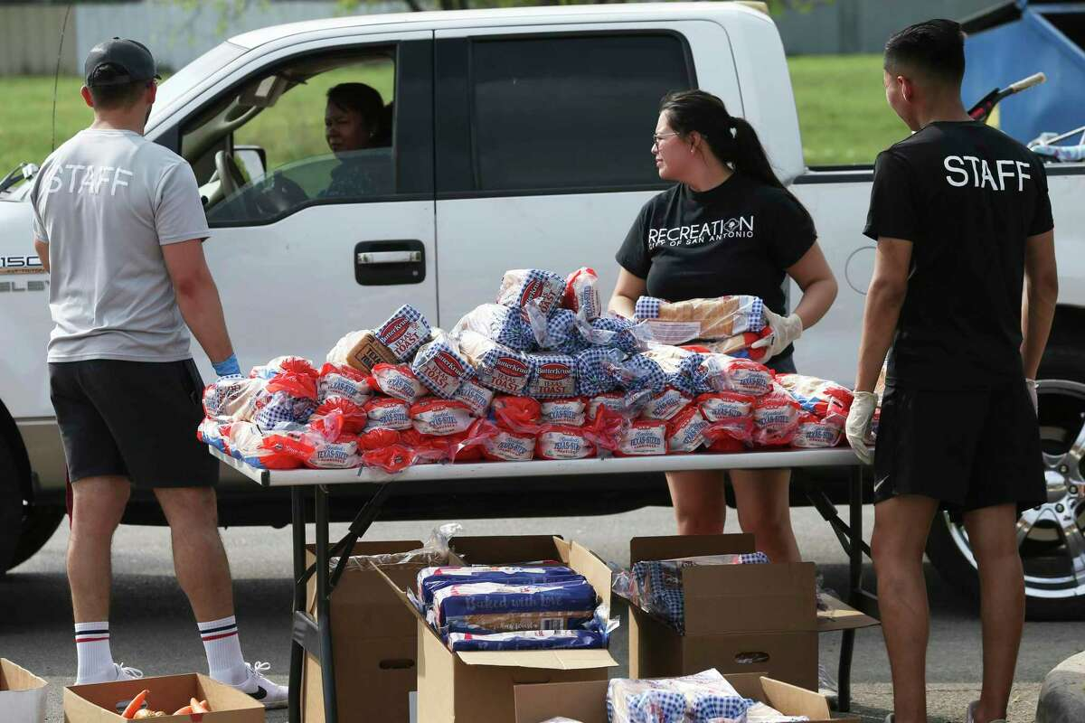 City Parks and Recreation personnel hand out food stuffs provided by the San Antonio Food Bank for distribution to those in need at Gilbert Garza Park on March 19, 2020.