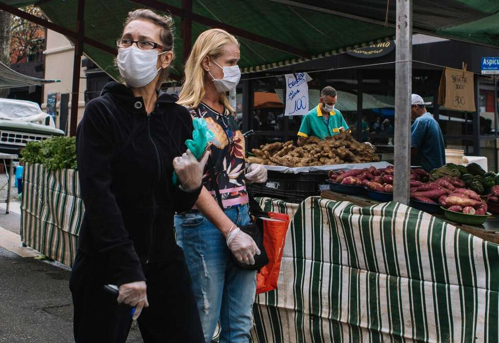SAO PAULO, BRAZIL - MARCH 21: Customers wearing masks walk in a street market during a lockdown aimed at stopping the spread of the (COVID-19) coronavirus pandemic on March 21, 2020, in Sao Paulo, Brazil. Sao Paulo state government authorities imposed restrictions to public transport and a mandatory shut-down of all non-essential businesses. According to the Ministry of Health, as of Friday, March 20, Brazil had 1.128 confirmed cases of the coronavirus (COVID-19) and at least 18 recorded fatalities. (Photo by Rebeca Figueiredo Amorim/Getty Images)