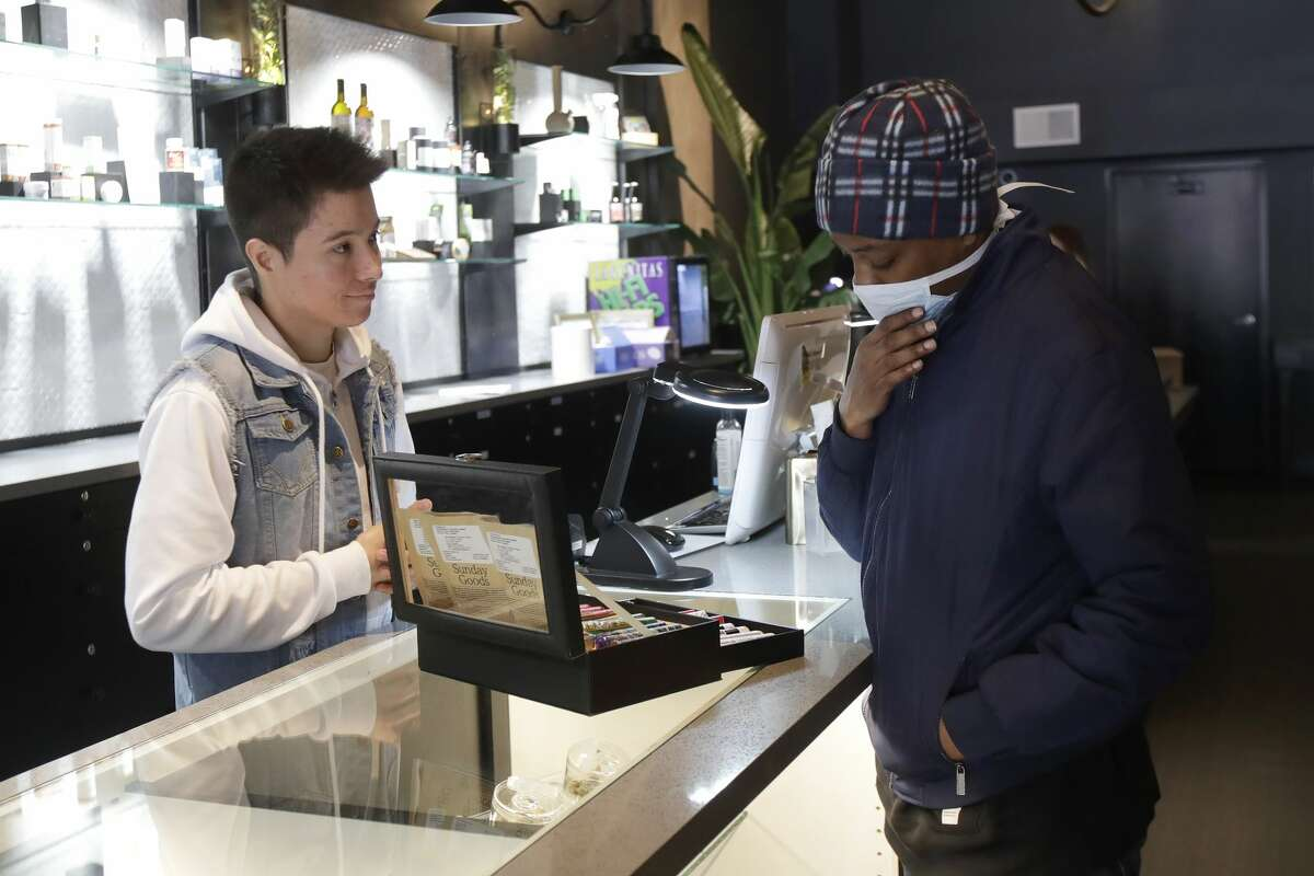 Customer Antoine Conners, right, wears a mask while being helped by budtender Chris Gomez at The Mission Cannabis Club dispensary in San Francisco, Thursday, March 19, 2020.