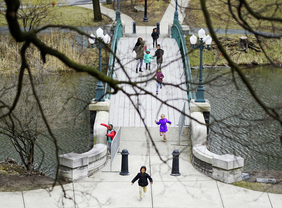 Children run across the bridge at Washington Park on an outing on Thursday, March 19, 2020, in Albany.