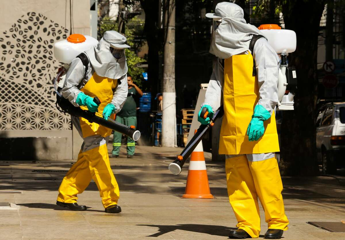 NITEROI, BRAZIL - MARCH 23: Members of a cleaning crew wearing protective suits spray public places with a disinfectant solution at Icarai neighborhood on March 23, 2020 in Niteroi, Brazil. These measures are aimed at stopping the spreading of the coronavirus (COVID-19) pandemic. According to the Ministry of Health, as of Monday, March 23, Brazil had 1.546 confirmed cases of the coronavirus (COVID-19) and at least 25 recorded deaths. (Photo by Luis Alvarenga/Getty Images)