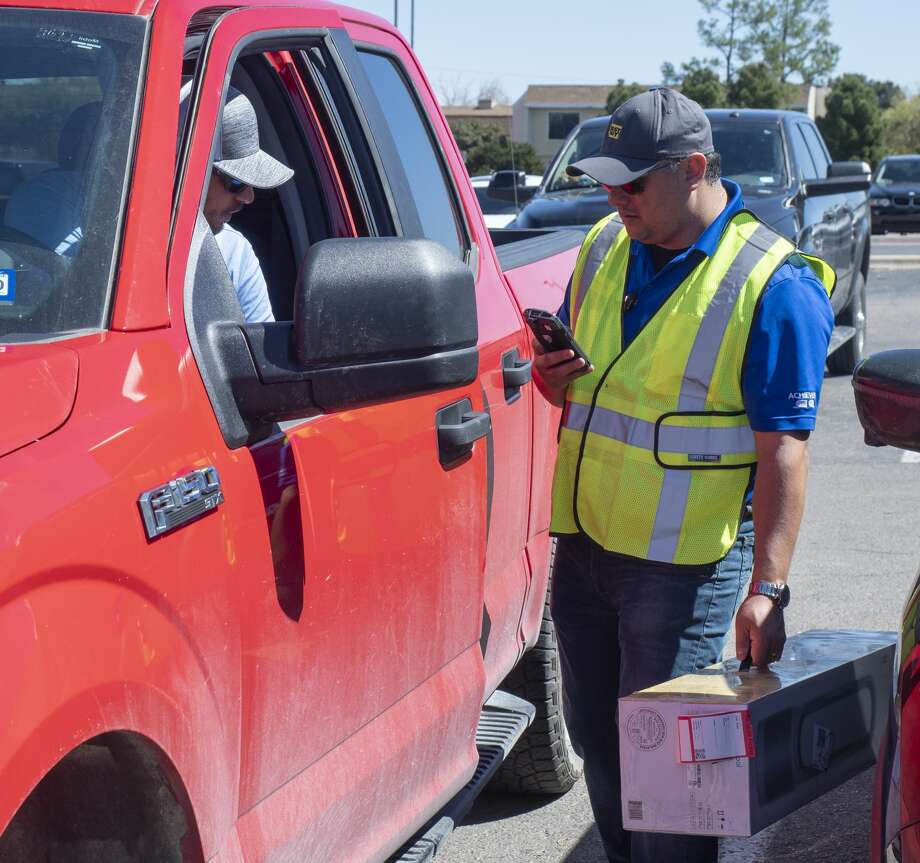 Carlos Frias, store manager, delivers a fan to Paiten Tinar 03/24/2020 outside Best Buy. Best Buy is open for online orders and will deliver to your car. Tim Fischer/Reporter-Telegram Photo: Tim Fischer/Midland Reporter-Telegram