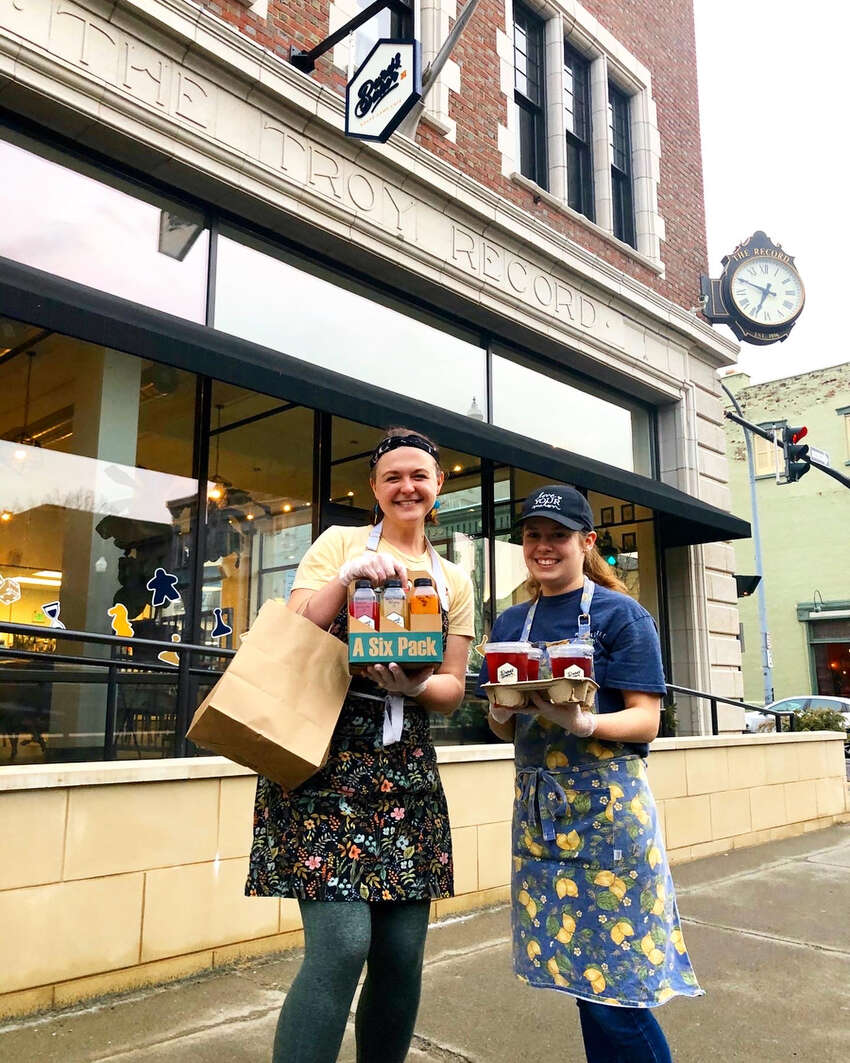 Charlotte Guyton, left, owner of Bard & Baker in Troy, and employee Katelyn Aupperle bring out food and drink for a curbside pickup.