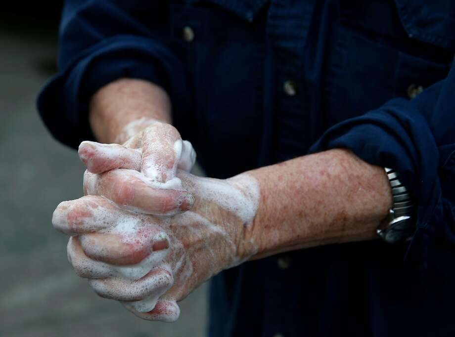 Annabelle Lenderink scrubs her hands while working at the Star Route Farms produce stand at the Ferry Plaza Farmers Market on March 21. Washing your hands before handling food should be enough to halt the spread of the coronavirus, according to experts. Photo: Paul Chinn / The Chronicle