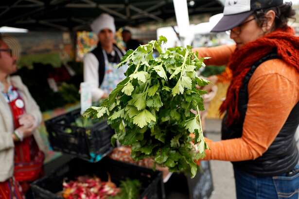 Vanya Goldberg of Oakland purchases vegetables from Gren Thumb Organics at the Berkeley Farmers Market on Shattuck Avenue in Berkeley, Calif., on Wednesday, March 19, 2020.