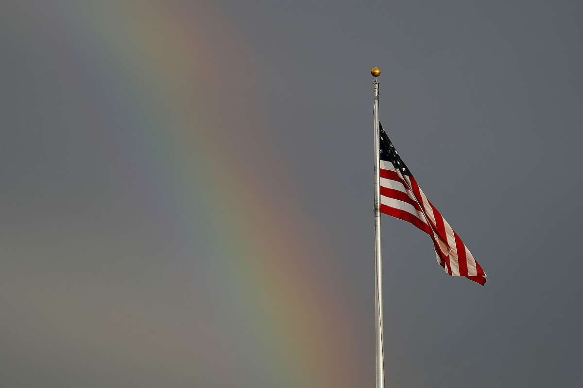 A rainbow is visible next to a United States flag along Route 49, Friday, March 20, 2020, in Hattiesburg, Miss. In a matter of days, millions of Americans have seen their lives upended by measures to curb the spread of the new coronavirus. For most people, the new coronavirus causes only mild or moderate symptoms. For some it can cause more severe illness. (AP Photo/Julio Cortez)