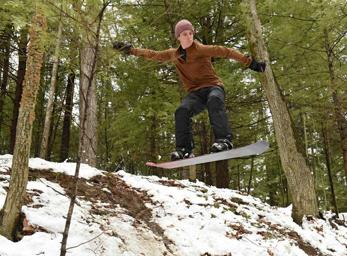 Cole Sgambati, 17, of Saratoga Springs flies down a hill on his snowboard through woods in Saratoga Spa State Park on Tuesday, March 24, 2020 in Saratoga Springs, N.Y (Lori Van Buren/Times Union)