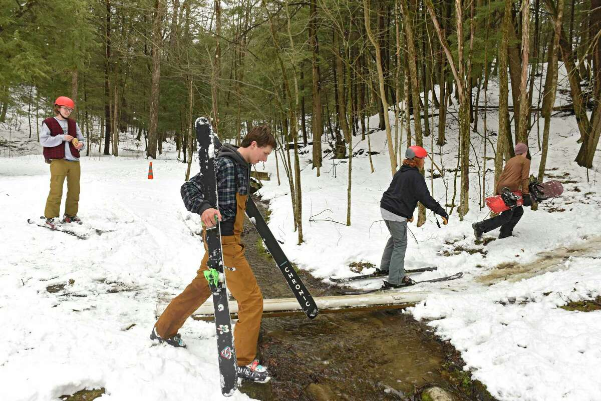 Teenagers from Saratoga Springs make the most of fresh fallen snow by snowboarding and skiing down hills in the woods in Saratoga Spa State Park on Tuesday, March 24, 2020 in Saratoga Springs, N.Y (Lori Van Buren/Times Union)