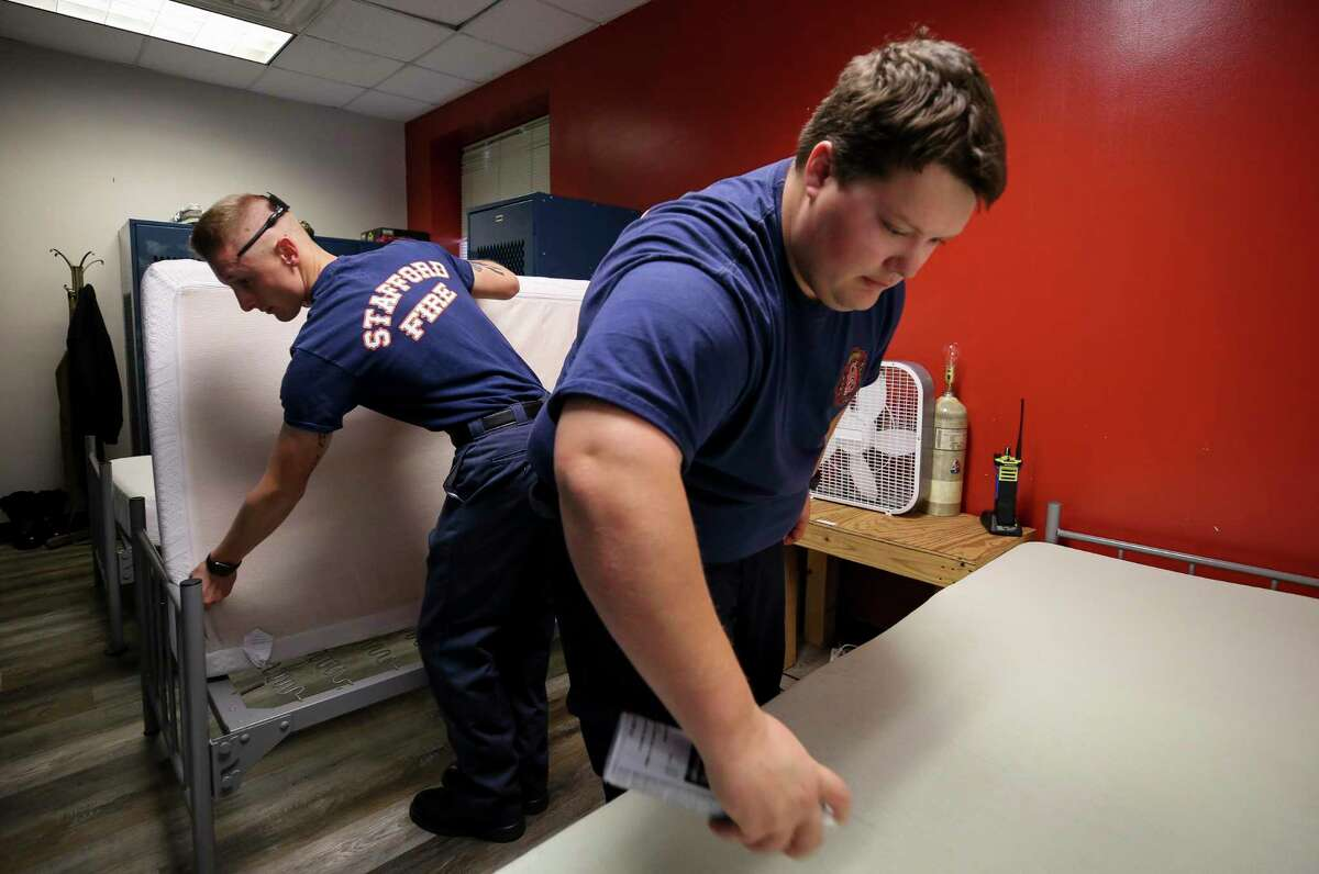Firefighters Matthew Bayes, right, and Braxton Cole, left, work to change out the fitted sheets and disinfects the mattresses they sleep on at the Stafford Fire Department Station 1 on Tuesday, March 24, 2020, in Stafford, Texas.