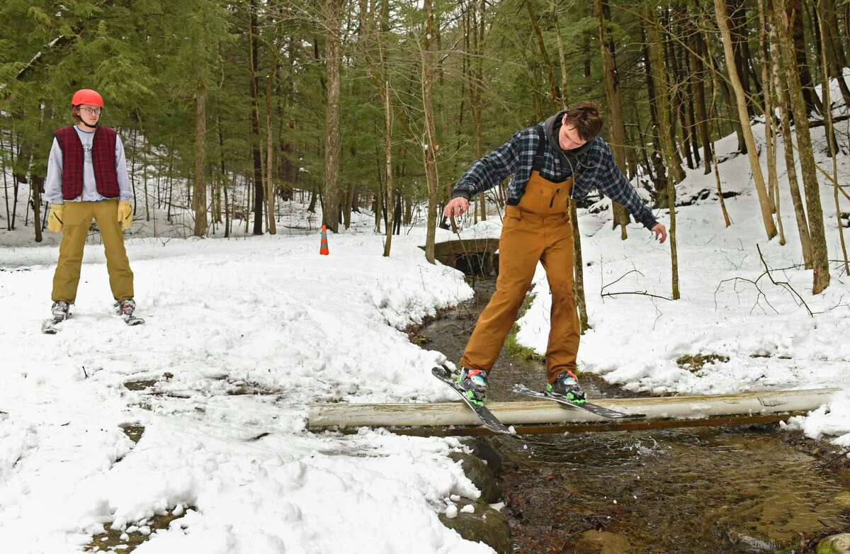 Henry Tucker, 18, of Saratoga Springs, left, watches as his friend Cam Sgambati, 19, ski down a hill in the woods and grind on a pipe they placed over a stream in Saratoga Spa State Park on Tuesday, March 24, 2020 in Saratoga Springs, N.Y (Lori Van Buren/Times Union)