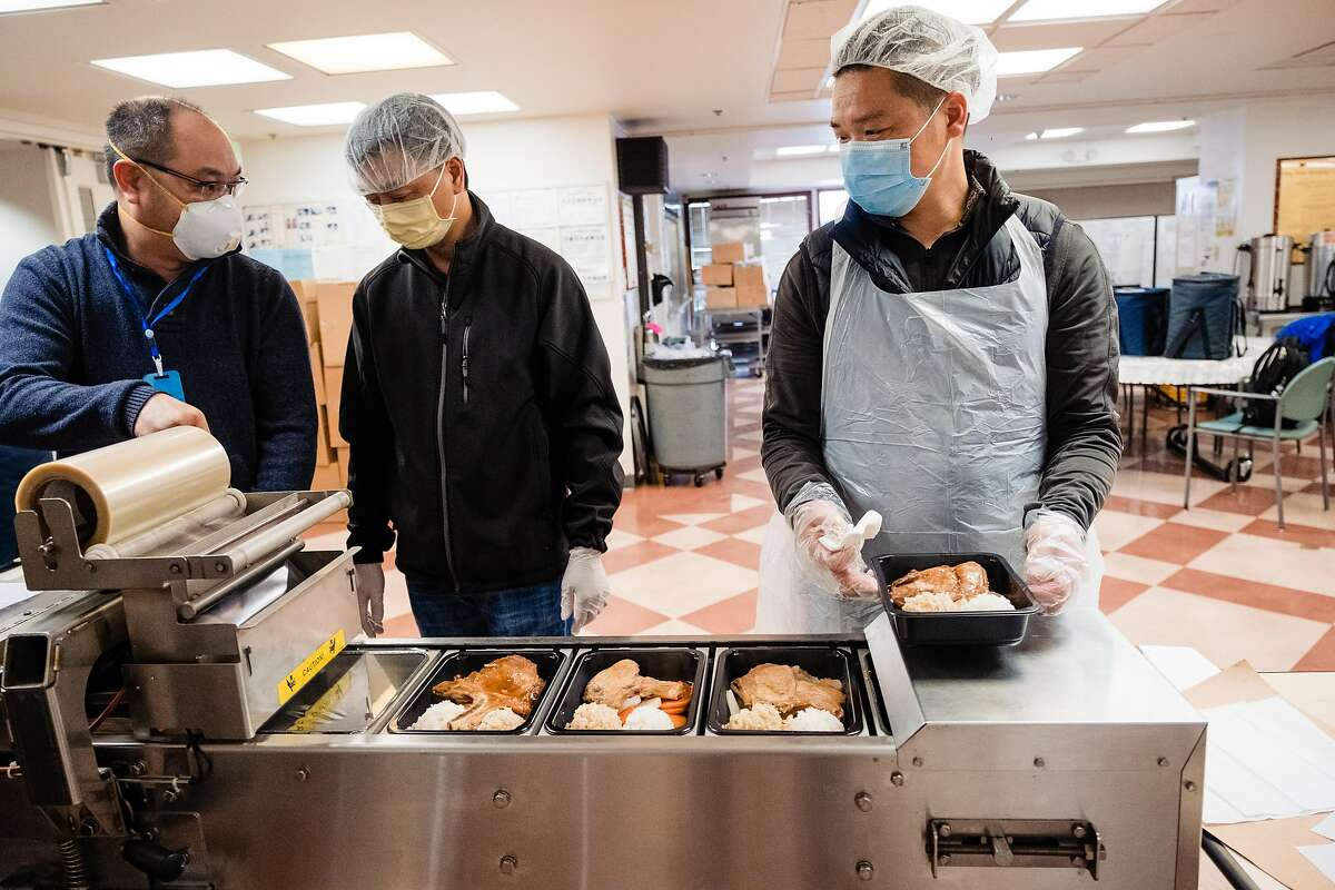 Stephen Ngan, left, Wei Ye, center and Chen Feng Bo run meals through a plastic wrapping machine meals before they get delivered to seniors at The Lady Shaw Senior Center in San Francisco, Calif. on Tuesday, March 24, 2020.