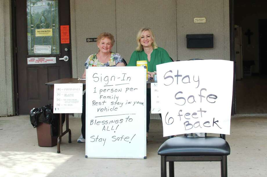 Christian Helping Hands volunteers Suzi Burns and Leigh Ann Veronneau have signs and smiles to greet people arriving to pick up food at the Pearland pantry. The group provides aid to under-served families in Pearland, Friendswood, Brookside Village and Manvel. Photo: Kirk Sides / Staff Photographer / © 2020 Kirk Sides / Houston Chronicle