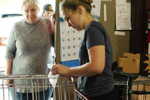 Hita Dickson, founder of Pearland's Christian Helping Hands, watches as Laura Thompson disinfects a shopping cart with wipes in March, after the food pantry saw the start of a surge in need from families affected by economic fallout from the coronavirus pandemic.
