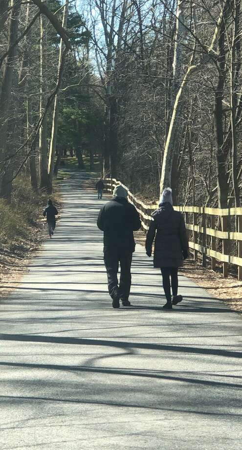 Residents are finding alternative ways to pass the time during the coronavirus pandemic. Above, residents take a walk Sunday at Harrybrooke Park in town. Photo: Deborah Rose / Hearst Connecticut Media