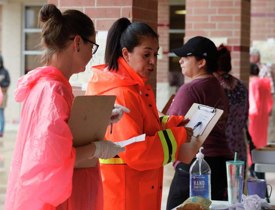 Elizabeth Thompson asks for student work for various subjects as teachers, faculty and staff distribute packets of schoolwork and supplies to students at Bozman Intermediate School, Friday, March 20, 2020, in Conroe. The effort is part of Conroe ISD's plan to educate students remotely as schools remain close because of the coronavirus pandemic. Photo: Jason Fochtman, Houston Chronicle / Staff Photographer / Houston Chronicle  © 2020