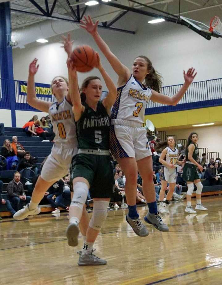 Morley Stanwood seniors Emma Doyle and Hailey Dard go up to block an attempt from Hesperia junior Emily Bayle during the regular season. (Pioneer file photo/Joe Judd)
