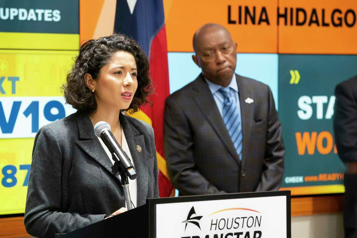 Harris County Judge Lina Hidalgo speaks as Houston Mayor Sylvester Turner listens during a press conference announcing that the county will adopt a